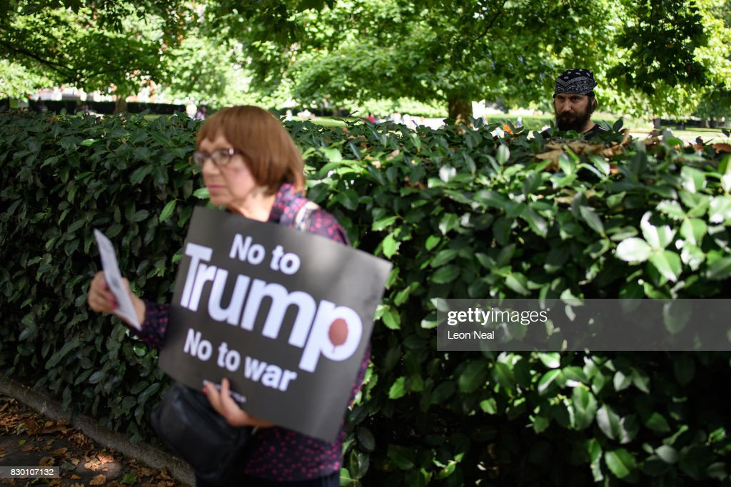 A man watches a woman as she holds a 'No to Trump' placard outside the U.S. embassy during a 'Stop the War' protest on August 11, 2017 in London, England. The group called the demonstration to campaign against the growing tensions between the U.S. and North Korea which they believe is being further fanned by Donald Trump's hardline statements.