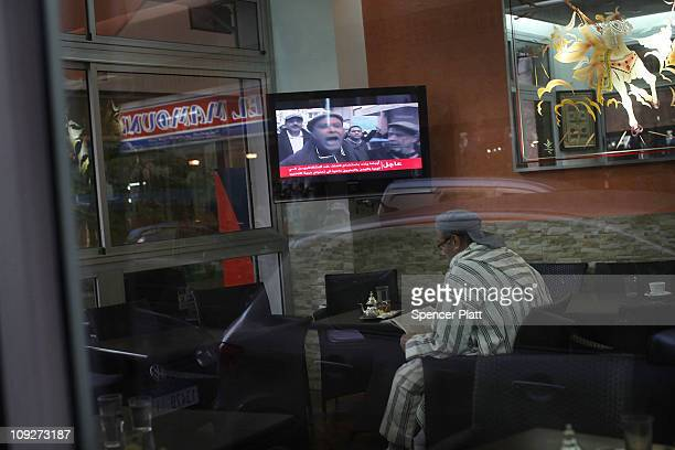 A man watches Al Jazeera in a cafe on February 18 2011 in Rabat Morocco Moroccan Facebook groups are calling for demonstrations this Sunday following...