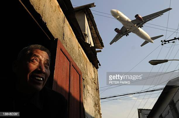 A man watches as an airliner flies over his house into Hongqiao International airport in Shanghai on January 5 2012 Chinese airlines will not pay a...