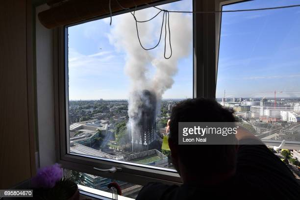 A man watches as smoke continues to rise from the building after a huge fire engulfed the 24 storey residential Grenfell Tower block in Latimer Road...