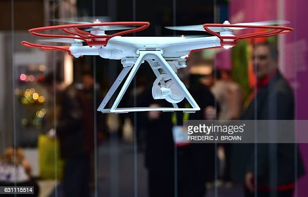 A man watches as someone flies the remote control Mi Drone from Xiomi a Smart Drone with 4k UHD camera and autopilot controls during the 2017...