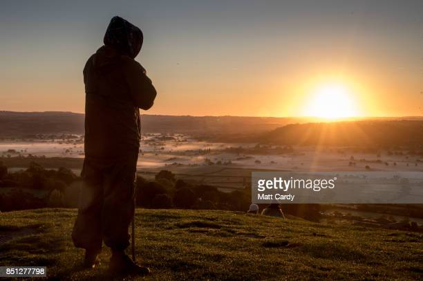 A man watches as the autumn sun rises over the Somerset Levels viewed from Glastonbury Tor near Glastonbury on September 22 2017 in Somerset England...