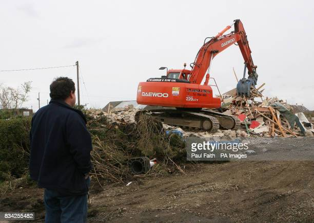 A man watches as the first of 17 houses are demolished near to City of Derry Airport
