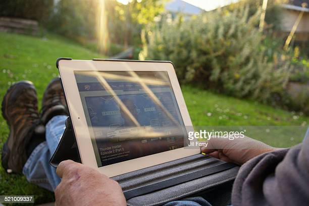 A man watches basketball on his iPad while sitting outside in his garden in the evening