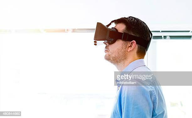 Man watches content displayed through virtual reality glasses