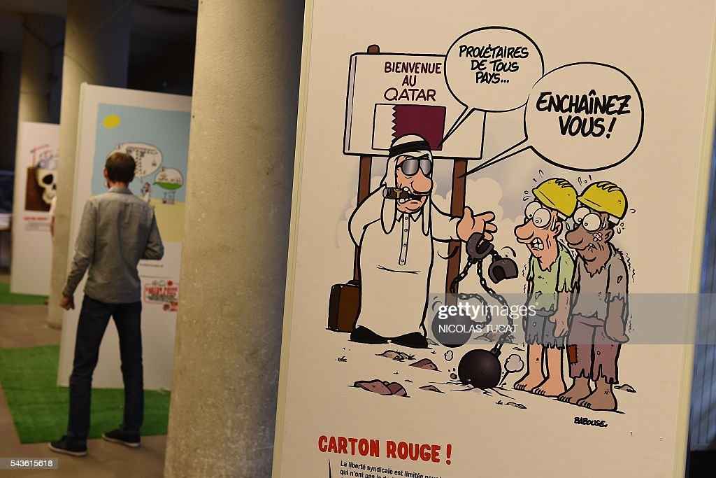 A man watches drawings of the 'Carton rouge a la FIFA' (A red card for the International Football Federation) exhibition on June 29, 2016 in Bordeaux, southwestern France. This exhibition by French General Confederation of Labour (CGT) workers union focuses on the exploitation of workers on the construction sites of major international competitions such as Quatar or Russia. The cartoon reads 'Welcome to Qatar. Proletarians of all countries, put those chains on'. / AFP / NICOLAS