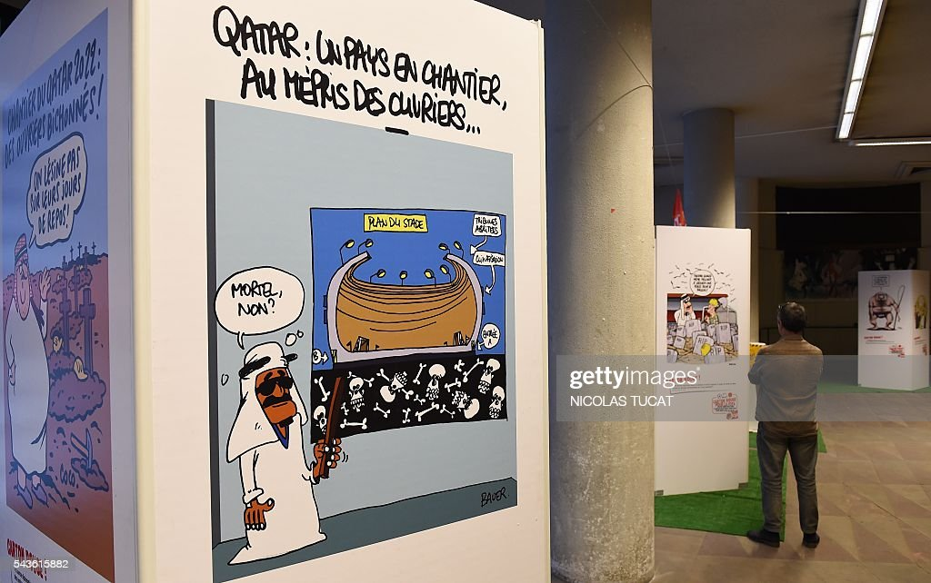 A man watches drawings of the 'Carton rouge a la FIFA' (A red card for the International Football Federation) exhibition on June 29, 2016 in Bordeaux, southwestern France. This exhibition by French General Confederation of Labour (CGT) workers union focuses on the exploitation of workers on the construction sites of major international competitions such as Quatar or Russia. The cartoon reads 'Qatar, a country under construction, in disregard of the workers'. / AFP / NICOLAS