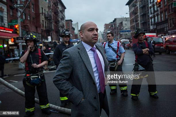 A man watches firefighters battle a blaze caused by an explosion that forced two buildings to collapse on Second Avenue in Manhattan's East Village...