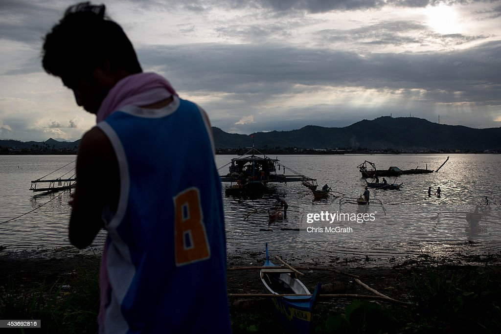 A man watches fishermen prepare their boats from the San Jose evacuation center on August 16, 2014 in Tacloban, Leyte, Philippines. Many families are still housed in temporary tent housing in the San Jose district. The families have been told that they will be rehoused before the visit of Pope Francis. Residents of Tacloban city and the surrounding areas continue to focus on rebuilding their lives nine months after Typhoon Haiyan struck the coast on November 8, 2013, leaving more than 6000 dead and many more homeless. With many businesses and government operations back up and running and with the recent start of the years typhoon season, permanent housing continues to be the main focus with many families still living in temporary accommodation. As well as continuing recovery efforts Leyte is preparing for the arrival of Pope Francis, who will visit the region from January 15- 19.
