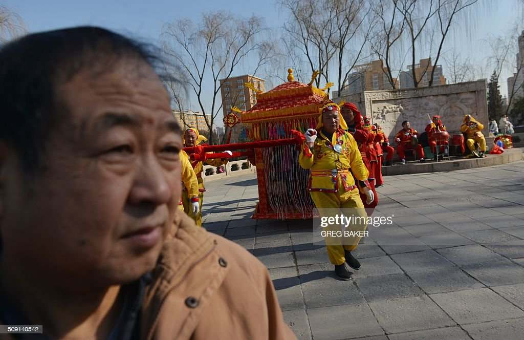 A man watches folk performers carry people in a sedan chair in a park in Beijing during Lunar New Year celebrations on February 9, 2016. Millions of Chinese are celebrating Spring Festival, the most important holiday on the Chinese calendar, which this year marks the beginning of the Year of the Monkey. AFP PHOTO / GREG BAKER / AFP / GREG BAKER