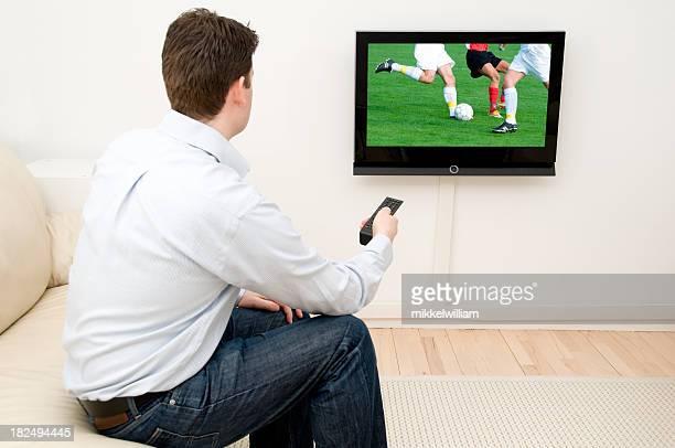 Uomo orologi partita di calcio in tv mentre i giocatori competono