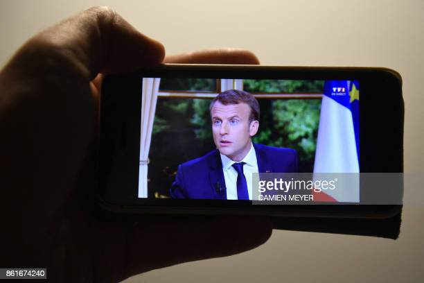 A man watches France's President Emmanuel Macron on a smartphone during the broadcast news of TF1 on October 15 2017 in Rennes western France / AFP...