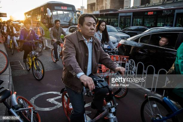 A man watches from a car as Chinese commuters crowd the bicycle lane as they ride bike shares during rush hour on April 11 2017 in Beijing China The...
