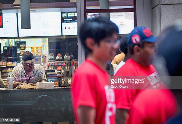 A man watches from inside a Mcdonald's restaurant as fast food workers and community activists protest outside on June 22 2015 in Chicago Illinois...