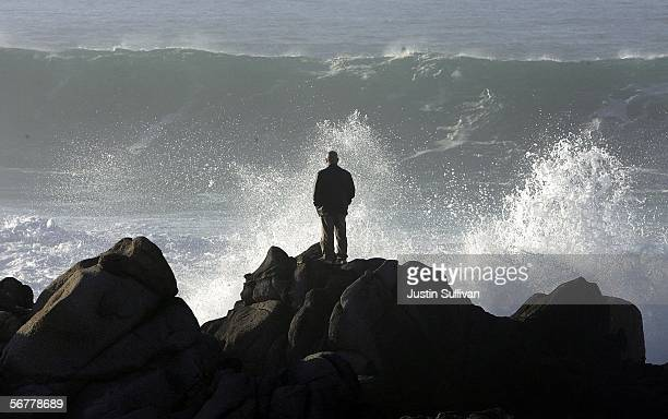 A man watches large waves crashing against rocks on February 7 2006 in Pacific Grove California The US saw its warmest January on record with a...