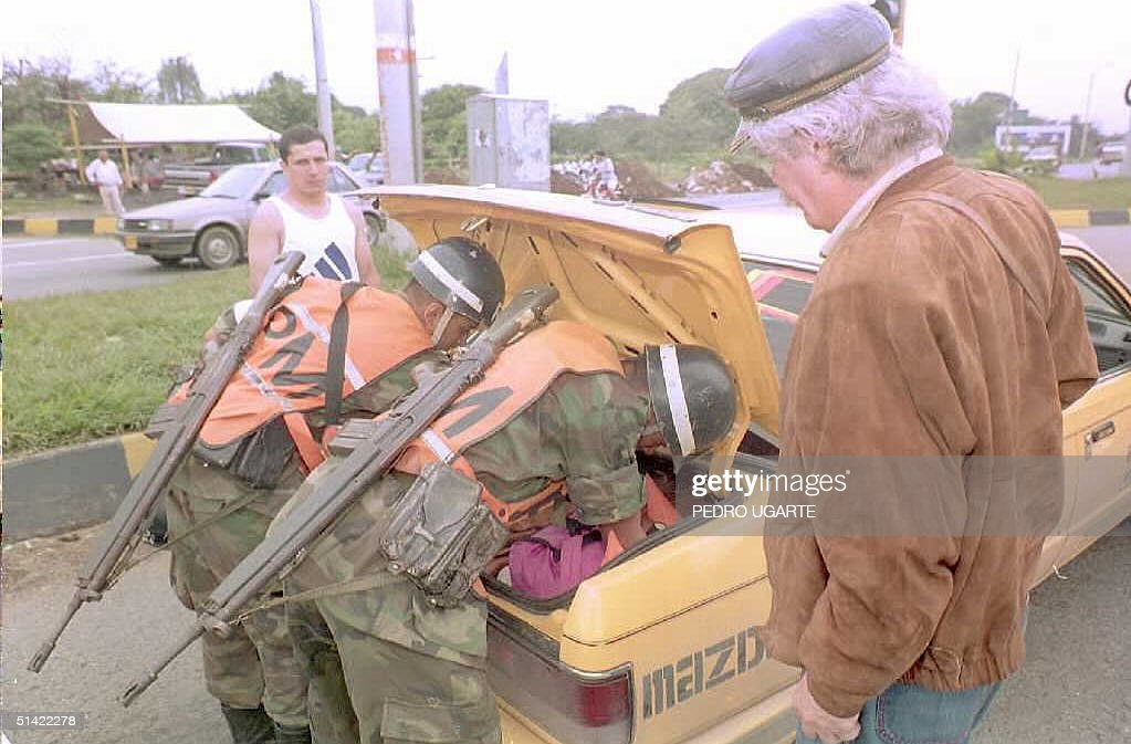 A man watches military police examine a taxi in Cali Colombia 155 miles southeast of Bogota In the last few days the police and the military have...