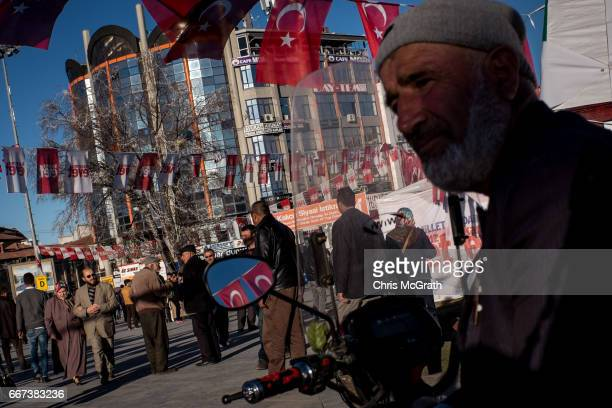 A man watches on as people walk past an Evet campaign tent in the main square on April 11 2017 in Sivas Turkey Campaigning by both the 'Evet' and...