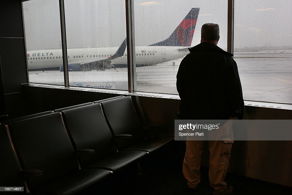 A man watches one of the last flights to arrive after many were cancelled due to a storm at LaGuardia Airport on November 7, 2012 in New York City. The Northeast suffered another storm today as a mix of snow, rain and high winds moved through the area, canceling flights and creating hazardous driving conditions. Six thousand households in the area are still without power for more than nine days following Superstorm Sandy.