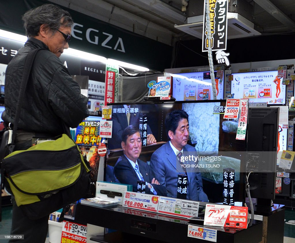 A man watches opposition LDP president Shinzo Abe on TV as Abe is elected as Japan's Prime Minister, at an electric shop in Tokyo on december 26, 2012. Abe was elected Japan's prime minister by the lower house of parliament after he swept to power on a hawkish platform of getting tough on diplomacy while fixing the economy. AFP PHOTO / Yoshikazu TSUNO