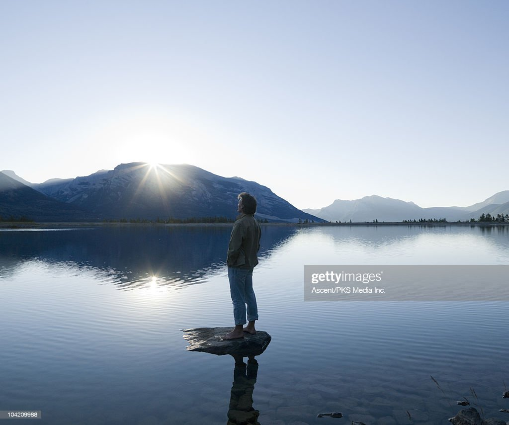 Man watches sunrise over mountains, on rock island : Stock Photo