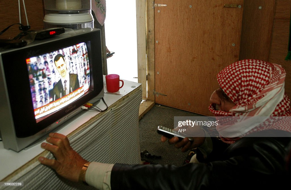 A man watches Syrian President Bashar al-Assad deliver a televised speech in the southern Lebanese city of Sidon on January 6, 2013. Assad outlined a three-phase plan to resolve the 21-month conflict in his country in which, according to the UN, more than 60,000 people have died.