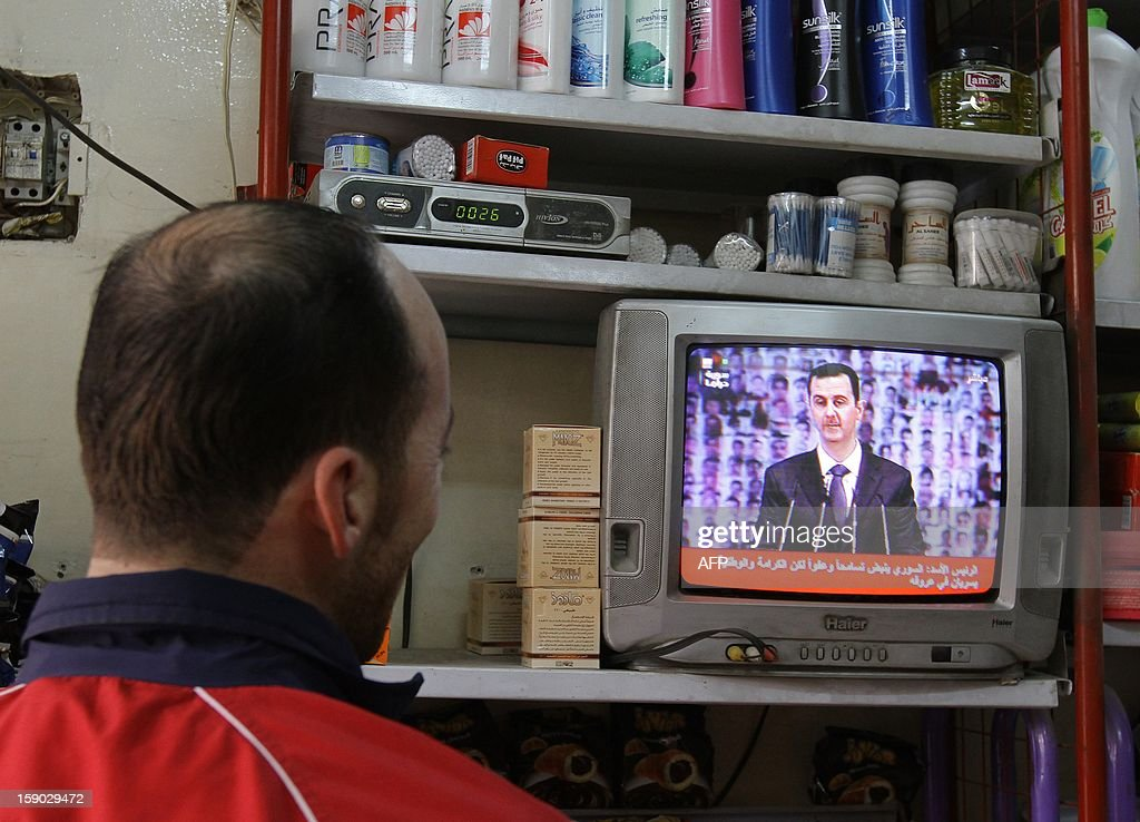 A man watches Syria's embattled President Bashar al-Assad making a public address on the state-run Syrian TV, on January 6, 2013 in Damascus. Bashar al-Assad in a rare speech Sunday denounced the opposition as 'slaves' of the West and called for a national dialogue conference to be followed by a referendum on a national charter and parliamentary elections.