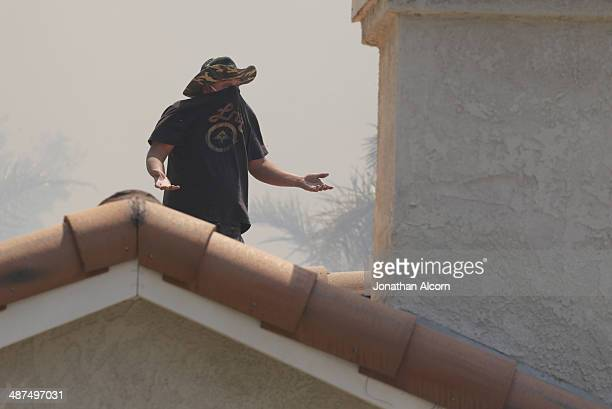 A man watches the approaching wind driven Etiwanda fire burning towards his home on April 30 2014 in Rancho Cucamonga California Flames from the fire...