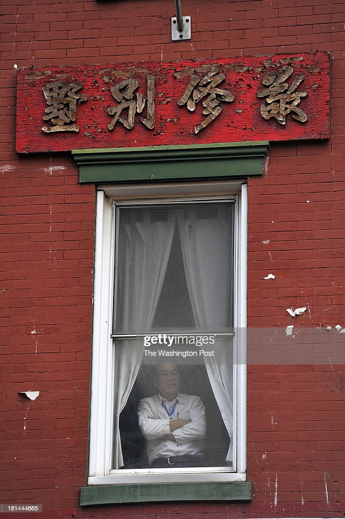 A man watches the Chinese New Year celebration from a window on Sunday February 10, 2013 in Washington, DC. Scores of people turned out for the event that ushers in the year of the Snake.