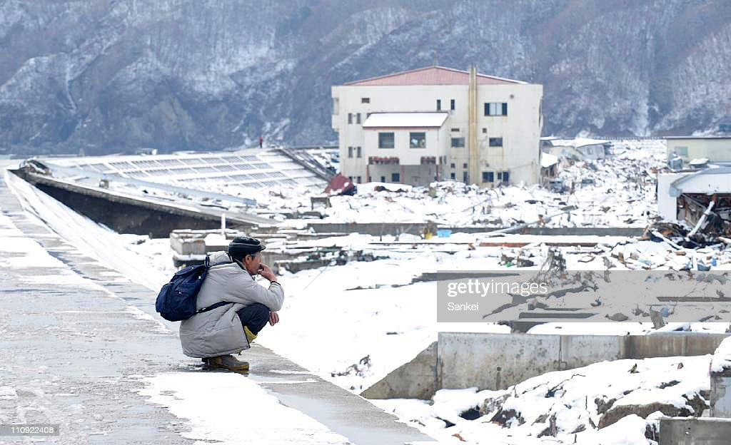 A man watches the destroyed Miyako city center from a breakwater on March 26, 2011 in Miyako, Iwate, Japan. The 9.0 magnitude strong earthquake struck offshore on March 11 at 2:46pm local time, triggering a tsunami wave of up to ten metres that engulfed large parts of north-eastern Japan, and also damaging the Fukushima nuclear plant and threatening a nuclear catastrophe. The death toll continues to rise with numbers of dead and missing exceeding 20,000 in a tragedy not seen since World War II in Japan.