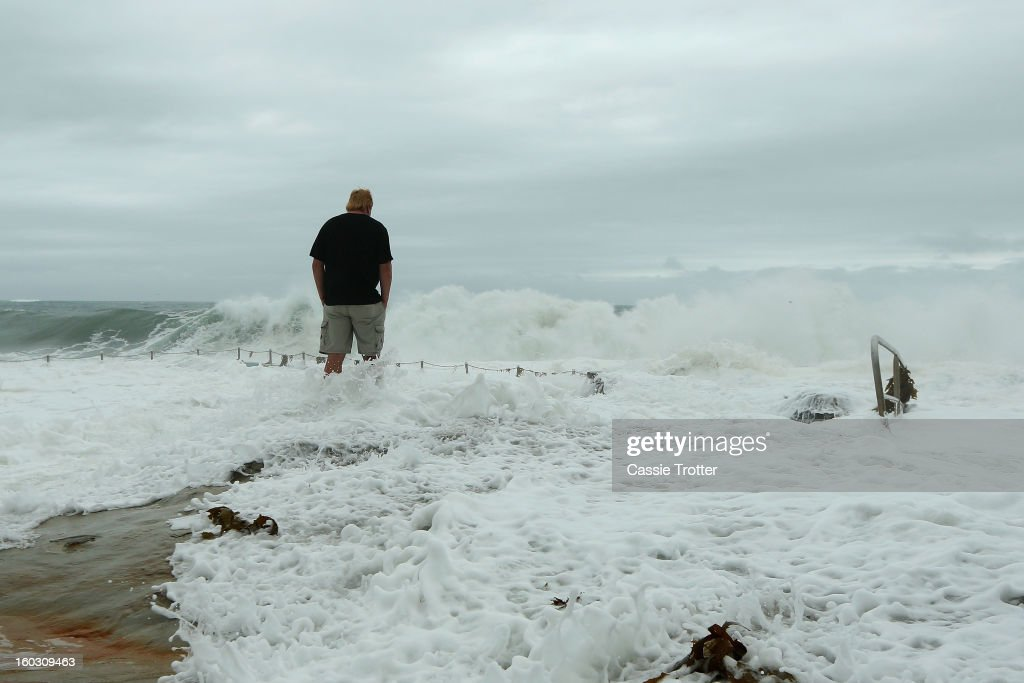 A man watches the large swell at the Dee Why baths after a storm overnight hit Sydney on January 29, 2013 in Sydney, Australia. Parts of Sydney are experienced record rainfall after ex-cyclone Oswald swept through the city last night.