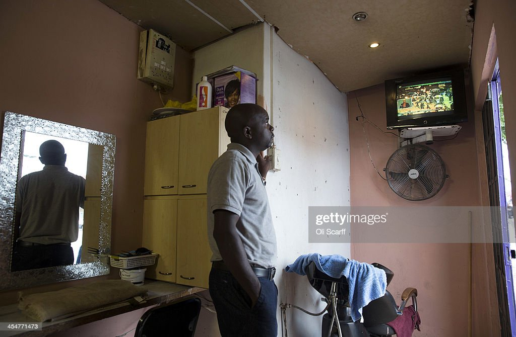 A man watches the official memorial service for Nelson Mandela on a television inside a barbers shop in Alexandra Township on December 10, 2013 in Johannesburg, South Africa. Over 60 heads of state have travelled to South Africa to attend a week of events commemorating the life of former South African President Nelson Mandela. Mr Mandela passed away on the evening of December 5, 2013 at his home in Houghton at the age of 95. Mandela became South Africa's first black president in 1994 after spending 27 years in jail for his activism against apartheid in a racially-divided South Africa.