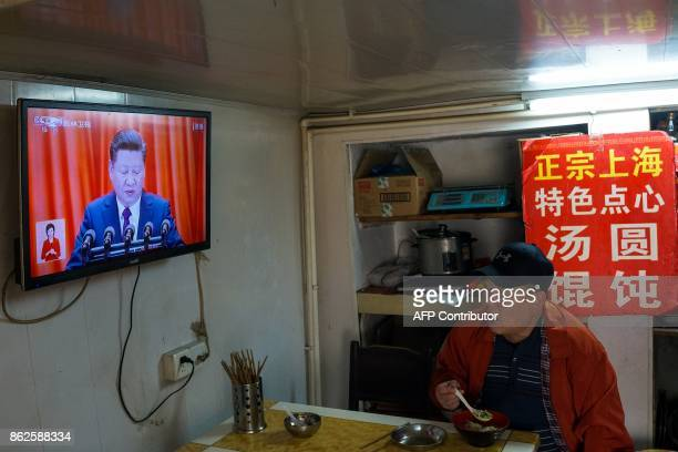 A man watches the opening of the 19th Communist Party Congress on a television in Shanghai on October 18 2017 The Chinese Communist Party opened its...