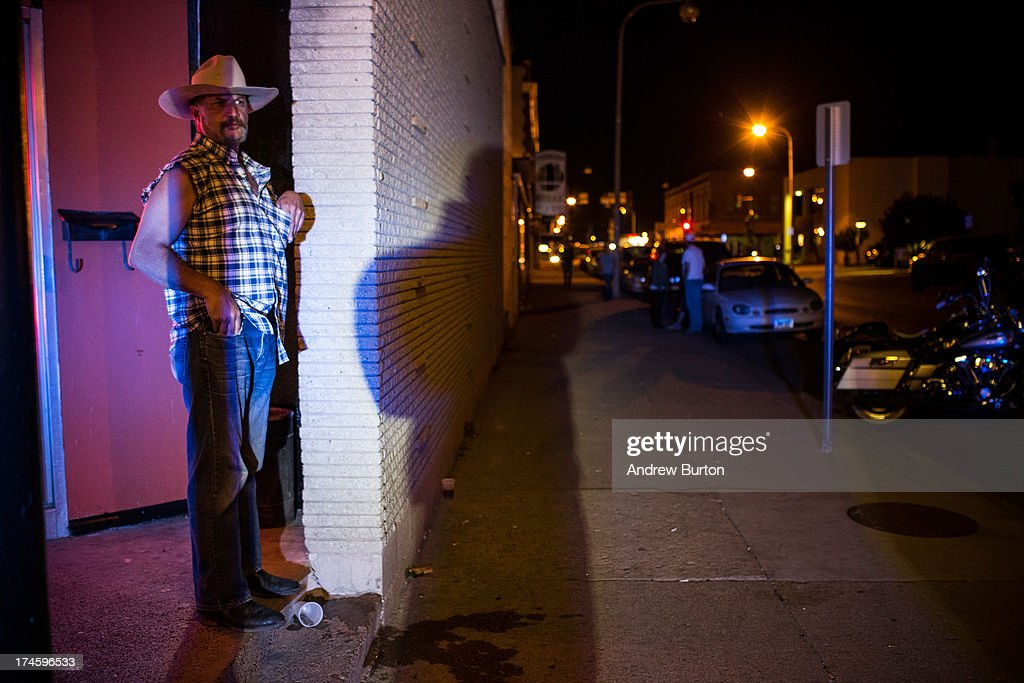 A man watches the police outside a bar after a fight on July 27, 2013 in Williston, North Dakota. The western region of North Dakota has seen a rise in crime, automobile accidents and drug usage recently, due in part to the oil boom which has brought tens of thousands of jobs to the region, lowering state unemployment and bringing a surplus to the state budget.