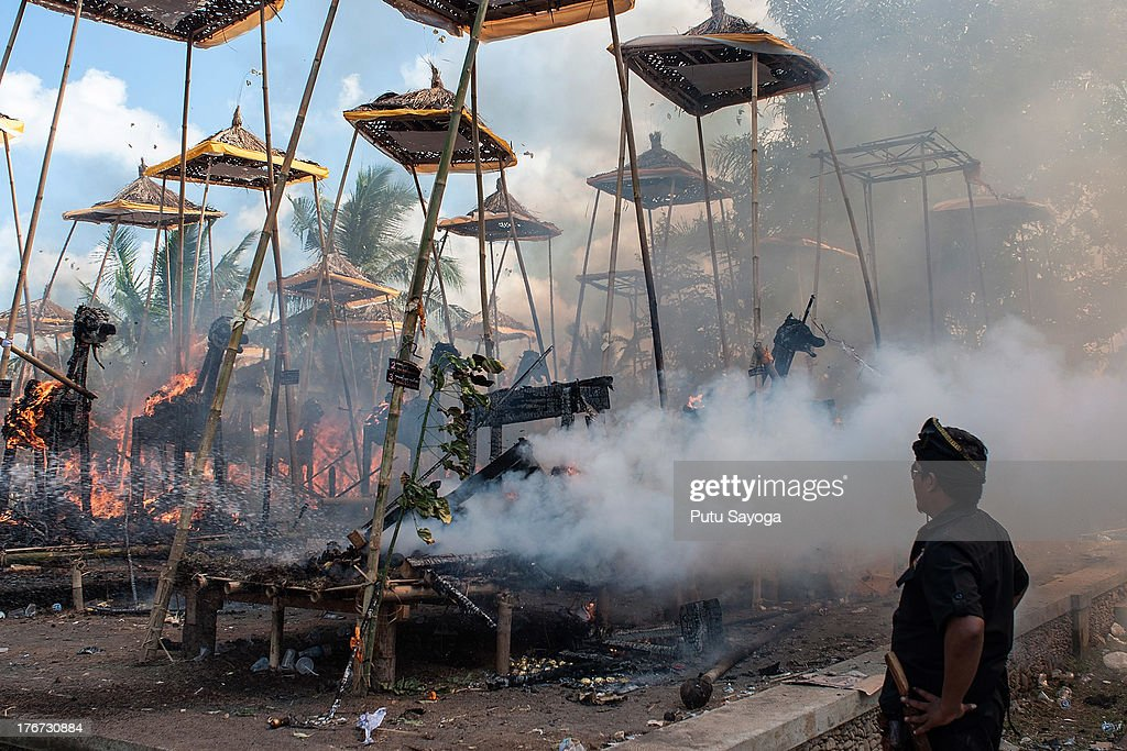 A man watches the sarcophagi burn at the cremation site during a Balinese Hindu mass cremation on August 18, 2013 in Ubud, Bali, Indonesia. More than 60 corpses were collectively cremated to share the expense of the ceremony. Well known as Ngaben, it is one of the most important ceremonies for Balinese Hindu people, as they believe it will free the spirit from the deceased body so it can reincarnate.