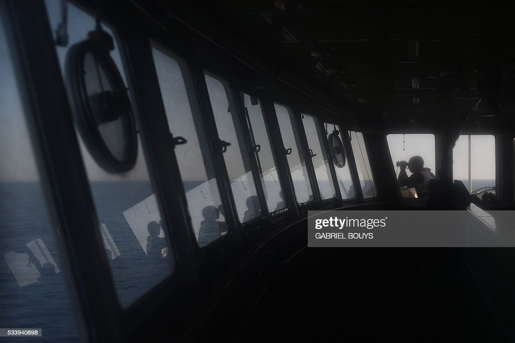 A man watches the sea with binoculars during a rescue operation at sea of migrants and refugees aboard the Aquarius, a former North Atlantic fisheries protection ship now used by humanitarians SOS Mediterranee and Medecins Sans Frontieres (Doctors without Borders), on May 24, 2016 in the Mediterranean sea in front of the Libyan coast. / AFP / GABRIEL