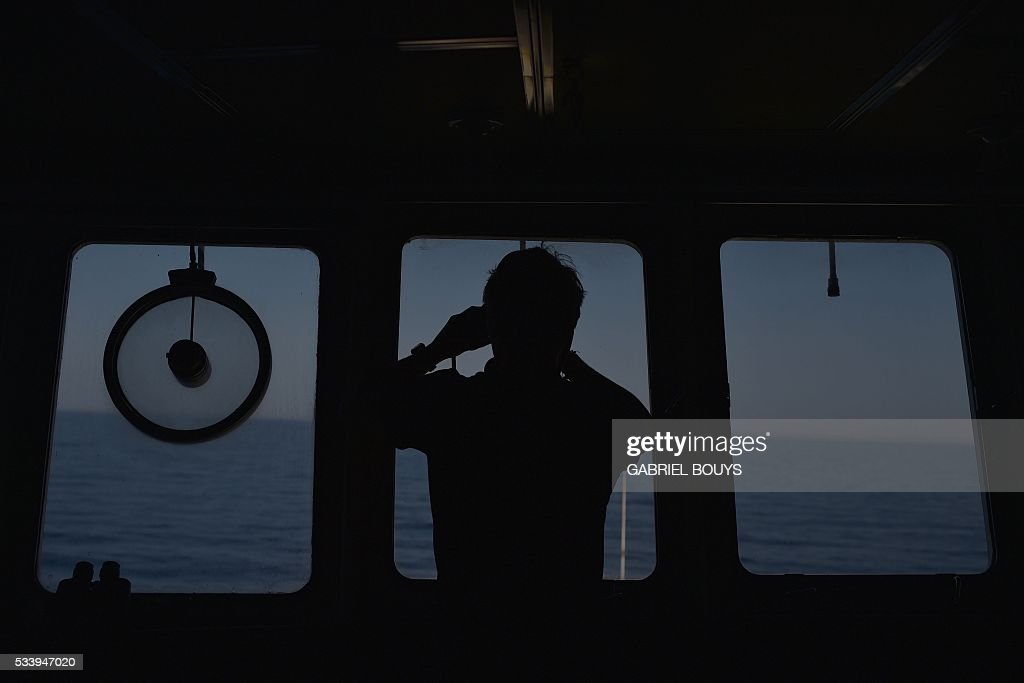 A man watches the sea with binoculars during a rescue operation of migrants and refugees of the 'Aquarius', a former North Atlantic fisheries protection ship now used by humanitarians SOS Mediterranee and Medecins Sans Frontieres (Doctors without Borders), on May 24, 2016 in the Mediterranean sea in front of the Libyan coast. / AFP / GABRIEL
