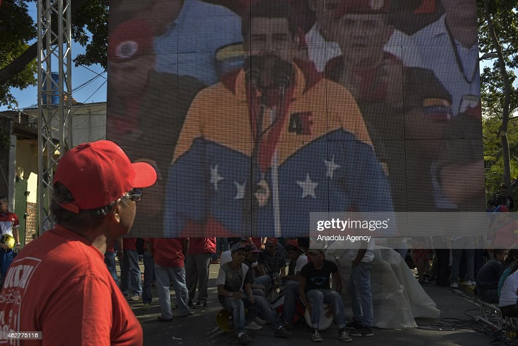 A man watches the speech of Nicolas Maduro on big screen during a military parade for the 23rd anniversary of attempted coup of Hugo Chavez against...