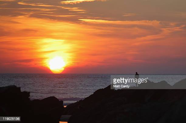 A man watches the sun setting over the sea from rocks at Fistral Beach on July 13 2011 in Newquay England With many state schools about to break for...