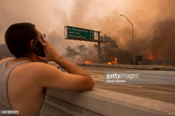 A man watches to see if his house and two of his cats on the other side of thick smoke and flames might burn near the community of Tujunga during the...