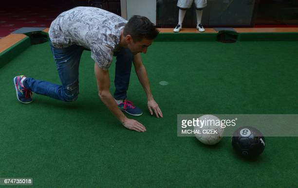 A man watches two balls during a footballpool match on April 28 2017 in Prague Footballpool is a combination of football and pool the sport uses...