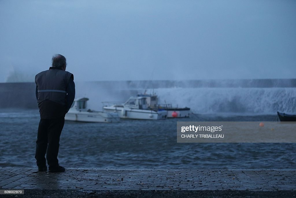 A man watches waves breaking in the harbour of Auderville, northwestern France, on February 8, 2016, as strong winds hit the region. Winds of over 130 kh/h were recorded in the region where 16 departments have been placed under alert for wind and flooding waves. / AFP / CHARLY TRIBALLEAU