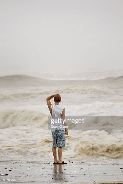 A man watches waves from Hurricane Ike slap the sea wall September 12 2008 in Galveston Texas The eye of the hurricane is expected to make landfall...