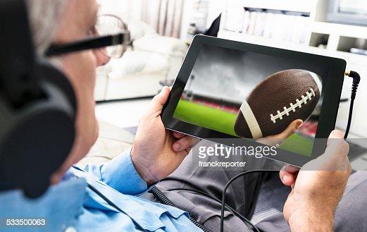 男性のサッカーの試合をご覧になり、タブレット