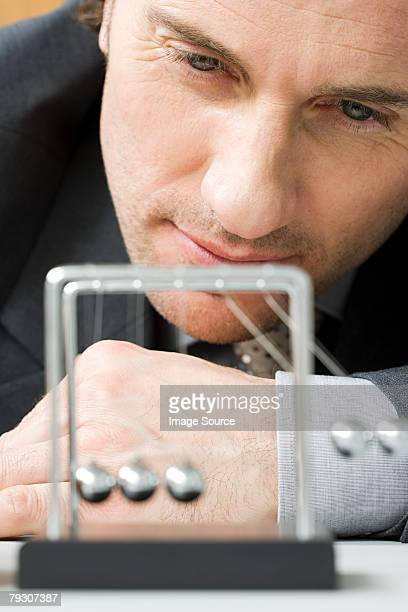 A man watching a newtons cradle in motion