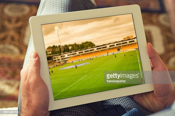 Man watching a soccer tv game on digital tablet