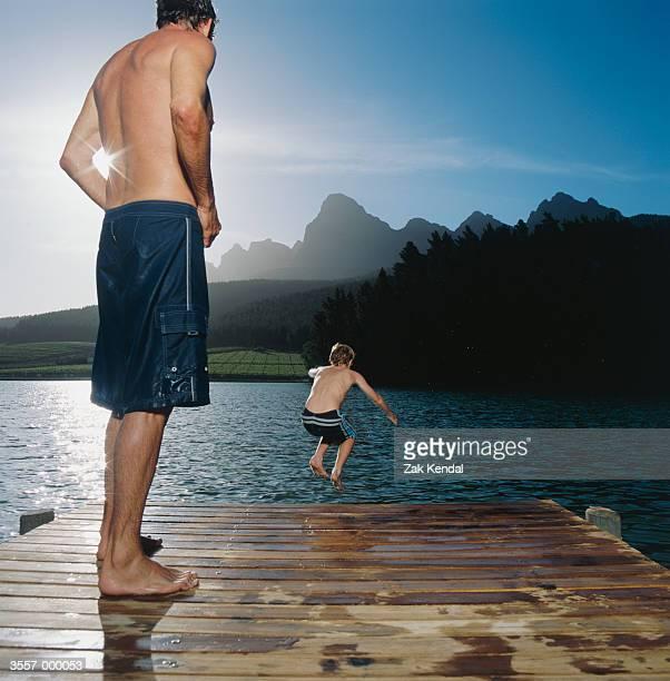 Man Watching Boy Jump in Lake
