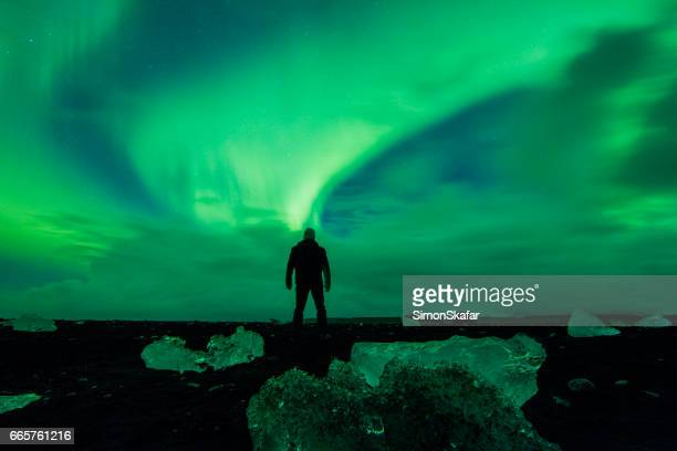 Man watching display of Aurora Borealis at beach