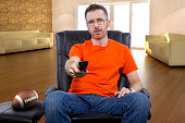 Front view of male sitting in a living room watching football on tv.  He is sitting down and relaxing by watching a game on TV.  The man is a sports fan.  The man is on his day off and is resting.  Th