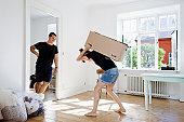 Man watching girlfriend carry heavy box
