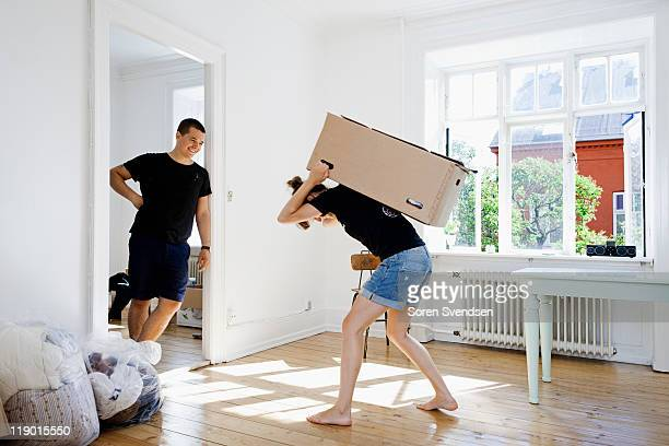 Man watching girlfriend carry heavy box